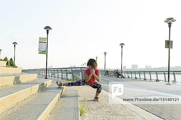Frau in voller Länge übt auf Stufen gegen den klaren Himmel