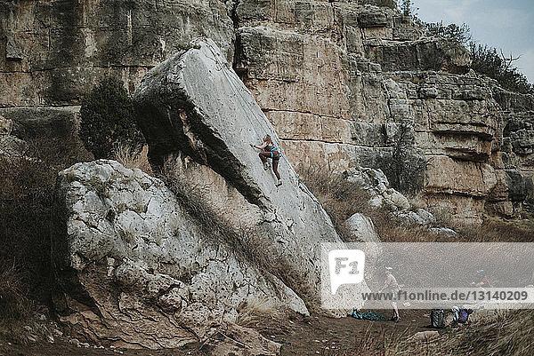 Männliche Freunde betrachten Frau beim Klettern am Fels im Wald