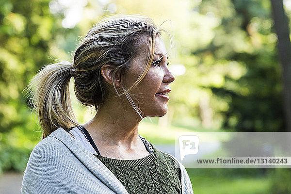 Nachdenkliche Frau schaut zum Park weg
