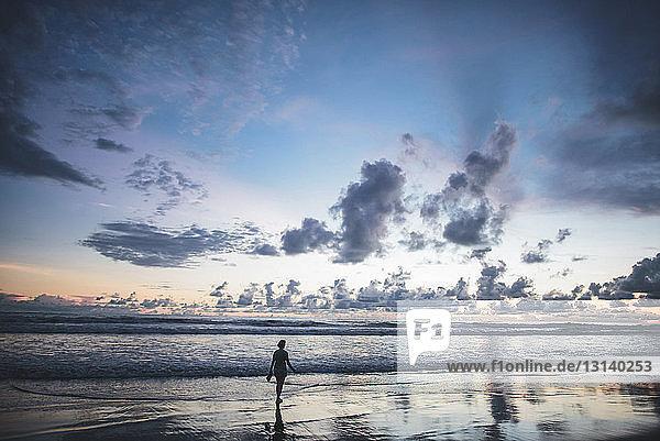 Rückansicht einer Frau  die bei Sonnenuntergang am Strand vor bewölktem Himmel steht