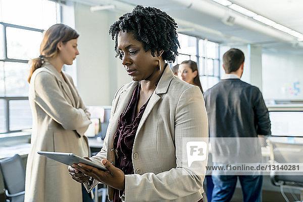 Geschäftsfrau benutzt digitales Tablet im Büro stehend