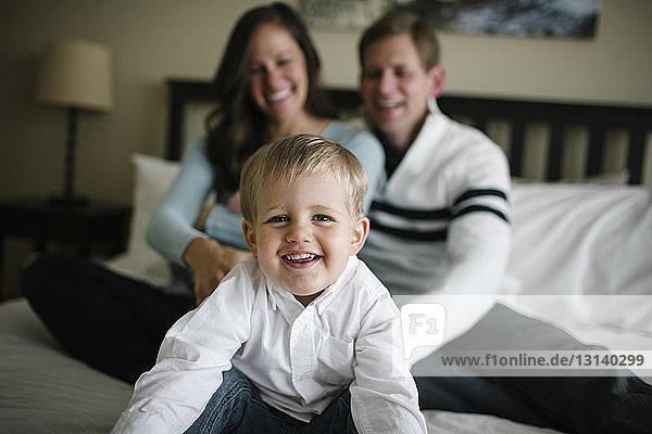 Porträt eines Sohnes  dessen Eltern zu Hause im Hintergrund auf dem Bett sitzen