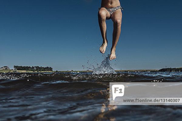 Unterer Teil eines Mädchens springt im See gegen klaren blauen Himmel