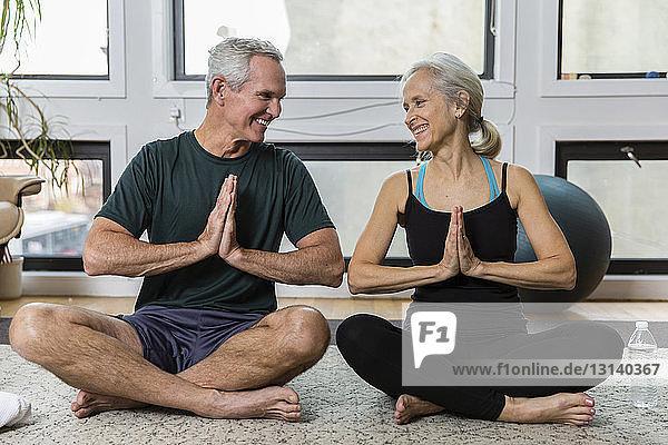 Lächelndes Paar in voller Länge mit gefalteten Händen  die sich bei der Meditation zu Hause von Angesicht zu Angesicht gegenüberstehen