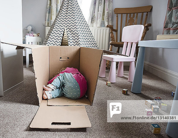 Playful girl relaxing in cardboard box at home
