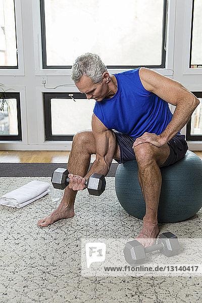 Ein muskulöser  reifer Mann in voller Länge  der eine Hantel hebt  während er zu Hause auf einem Fitnessball sitzt