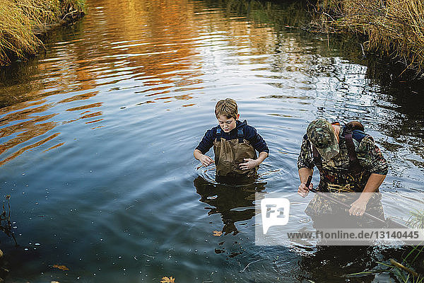 High angle view of father and son walking in lake at forest