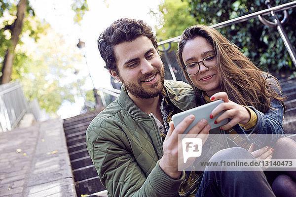 Glückliches junges Paar benutzt ein Smartphone,  während es auf einer Treppe sitzt