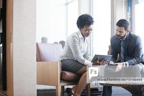 Geschäftsfrau zeigt einem männlichen Kollegen im Büro ein digitales Tablet