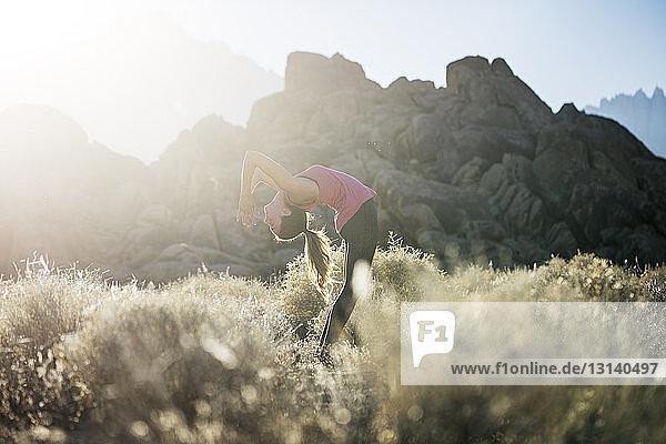 Frau praktiziert bei Sonnenschein Yoga auf Feld gegen Berge