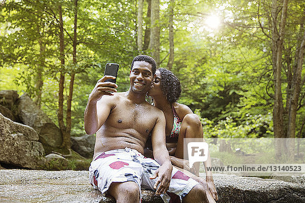 Woman kissing man taking selfie through smart phone on river bank in forest