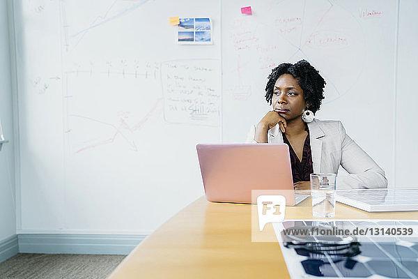 Nachdenkliche Geschäftsfrau mit Hand am Kinn  die im Büro an der Tafel sitzt