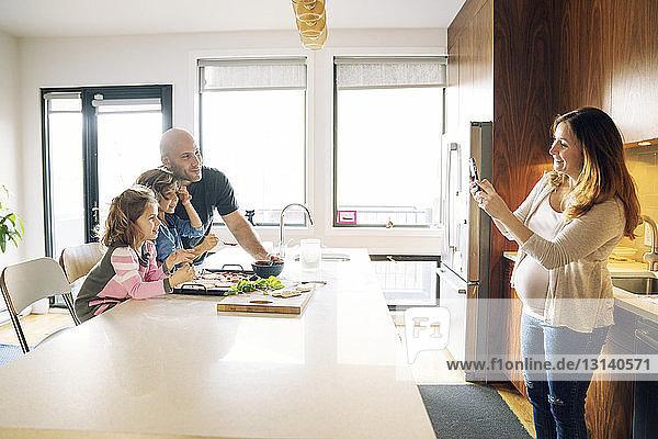 Schwangere Frau fotografiert Familie am Küchentisch zu Hause