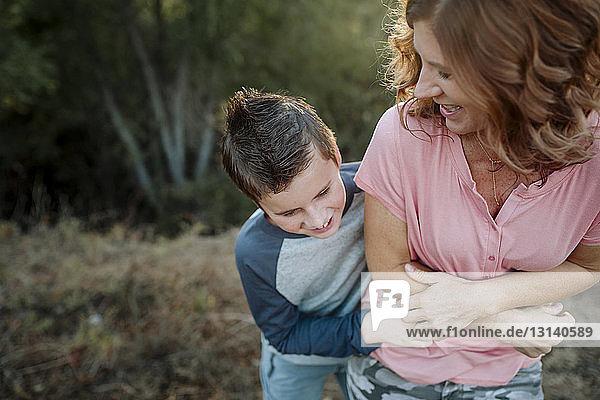 Glücklicher Sohn kitzelt Mutter  während er im Wald steht