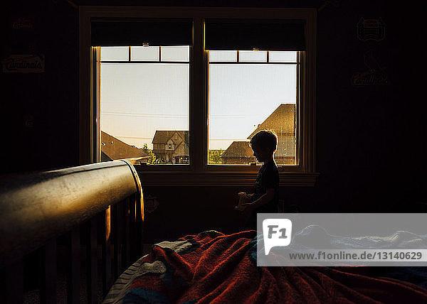 Boy standing by window in dark room