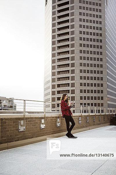 Frau in voller Länge  die ein Smartphone benutzt  während sie sich auf einem Geländer an der Terrasse gegen das Gebäude lehnt