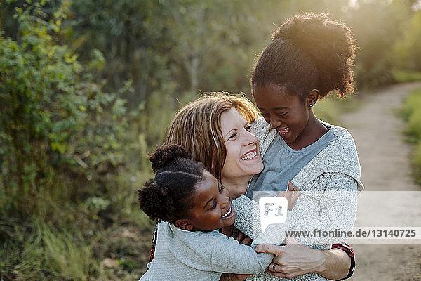 Fröhliche Mutter mit Töchtern im Park