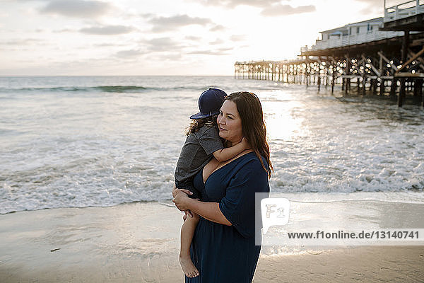 Thoughtful mother carrying son at beach against sky during sunset