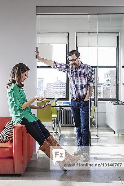 Glückliche Geschäftsfrau diskutiert über Tablet-Computer mit männlichem Kollegen im Kreativbüro