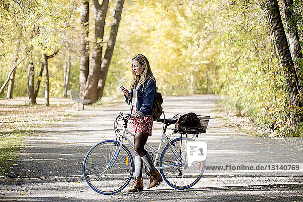Woman with bicycle using mobile phone while standing on road