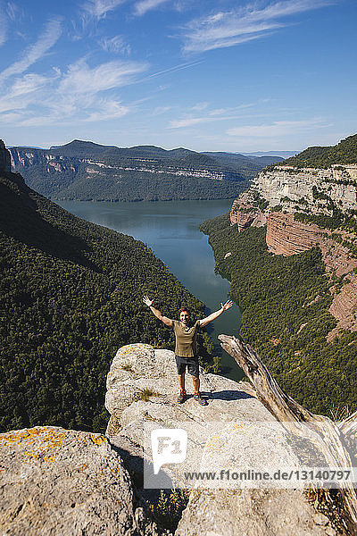 Portrait of male hiker with arms raised standing on mountain against blue sky during sunny day