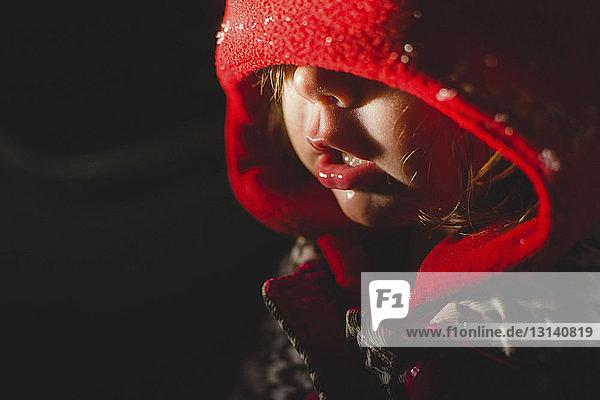 Nahaufnahme eines Mädchens mit Kapuzenkleidung in einem dunklen Raum