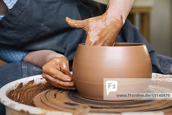 Midsection of woman molding clay in pottery wheel