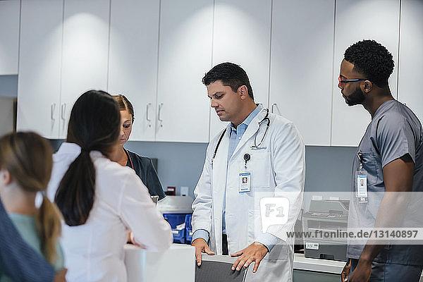 Ärzte  die am Krankenhausempfang mit dem Patienten im Vordergrund arbeiten