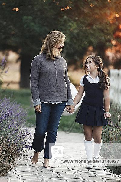 Glückliche Mutter und Tochter halten sich beim Hofgang an den Händen
