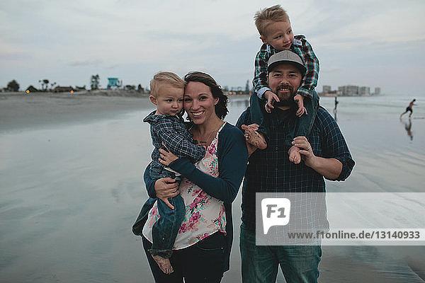 Fröhliche Eltern tragen Jungen,  während sie am Strand stehen