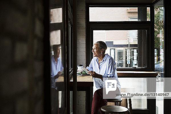 Lächelnde Frau liest Zeitung,  während sie durch das Fenster am Tisch im Cafe schaut