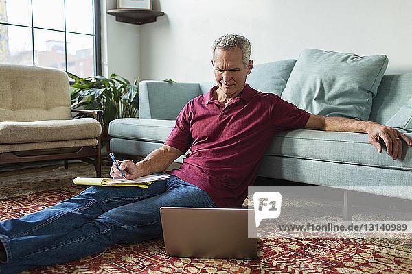 Ernsthaft reifer Mann  der einen Laptop benutzt  während er zu Hause im Wohnzimmer neben dem Sofa auf dem Teppich sitzt
