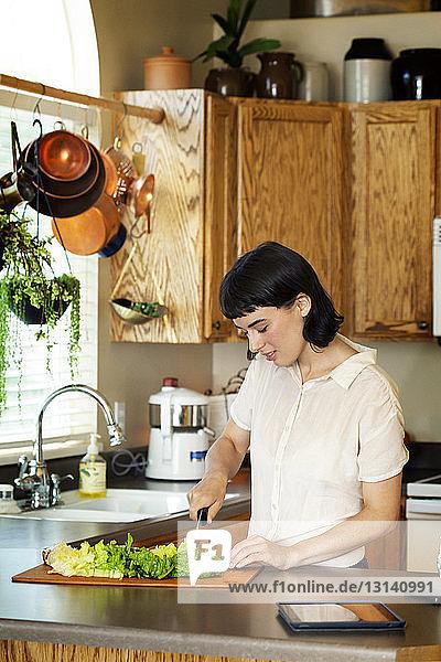 Lächelnde Frau schneidet frisches Gemüse  während sie zu Hause in der Küche steht