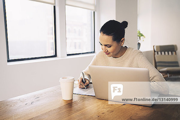 Businesswoman writing while sitting with laptop computer at desk in office