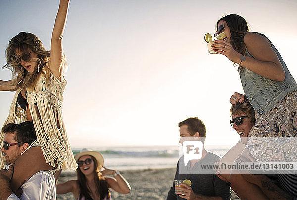 Fröhliche Freunde genießen am Strand