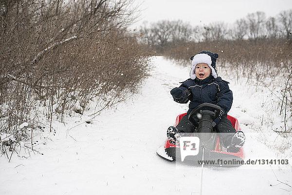 Full length of cute baby boy sitting on sled amidst snow