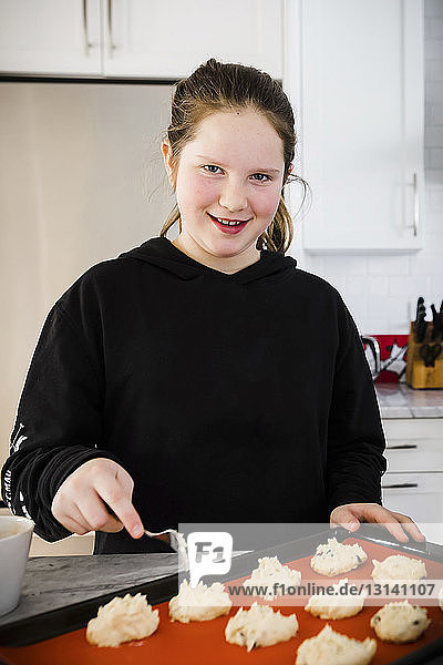 Porträt eines Mädchens  das zu Hause in der Küche Teig auf ein Backblech legt