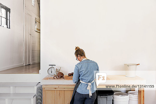 Rear view of woman working on earthenware at workplace