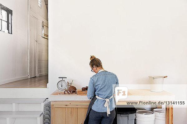 Rückansicht einer Frau  die am Arbeitsplatz mit Steingut arbeitet