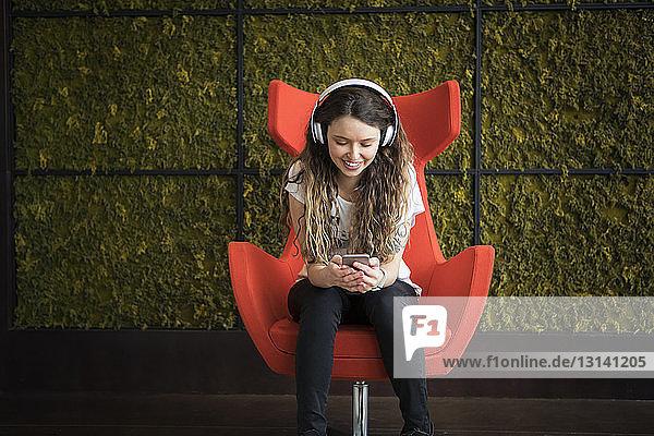 Frau  die Musik hört  während sie zu Hause auf einem Sessel sitzt