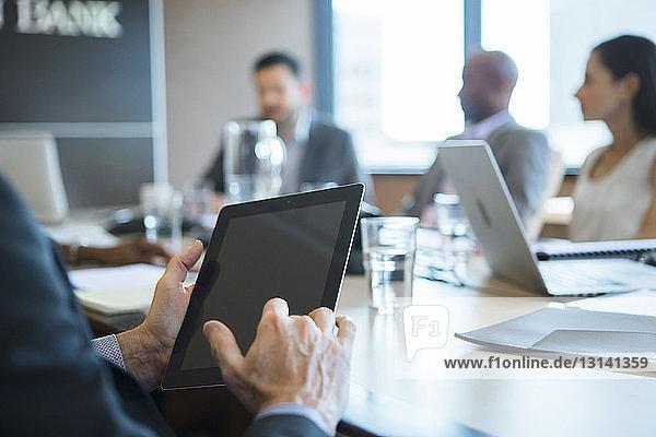 Abgetrennte Hände eines Geschäftsmannes  der in einer Besprechung einen Tablet-Computer benutzt