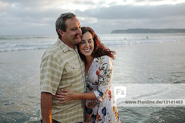 Glückliche Frau umarmt Mann  während sie am Strand wegschaut