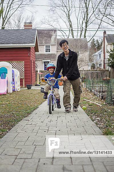 Glücklicher Vater hilft Sohn beim Fahrradfahren auf Fußweg im Hinterhof