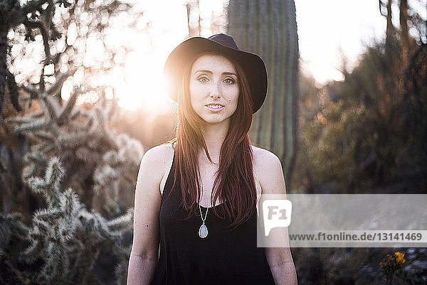Portrait of woman standing against trees during sunset