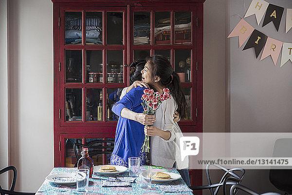 Glückliche Mutter und Tochter umarmen sich  während sie den Blumenstrauss zur Geburtstagsfeier halten