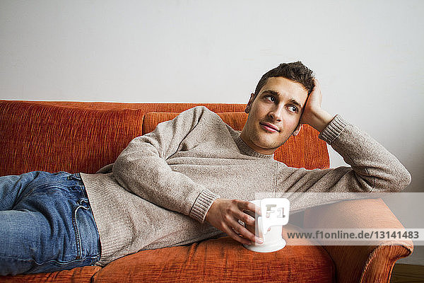 Thoughtful man holding coffee cup while lying on sofa at home
