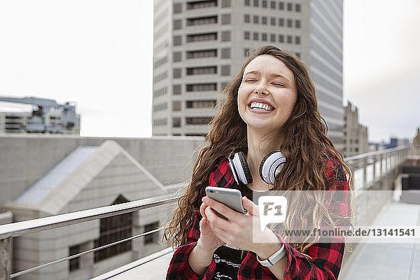Fröhliche Frau benutzt Smartphone  während sie im Terrassencafé steht