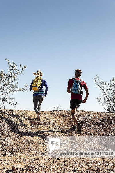 Rückansicht von Wanderern mit Rucksäcken  die am sonnigen Tag auf einem Hügel gegen den klaren Himmel laufen