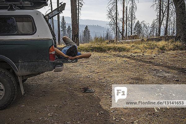 Mann entspannt sich auf Kofferraum im Wald