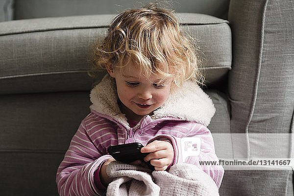 Girl using mobile phone while sitting by armchair at home